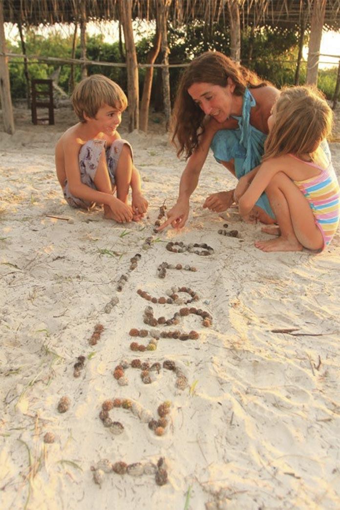 Cande Zapp y sus hijos dibujan números en la arenas