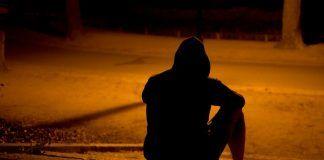 Joven solitario sentado de espaldas