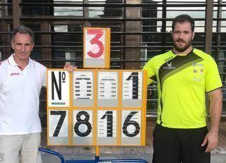 Javier Cienfuegos posa, junto a su entrenador Antonio Fuentes, con elk marcador de su nuevo record de Espana: 78,16 metros.